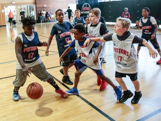 Pistons Academy attendee Jonnie Culbert, 8, far left, tries to protect the ball during a game at the Boll Family YMCA, Thursday, July 6, 2017 in Detroit.