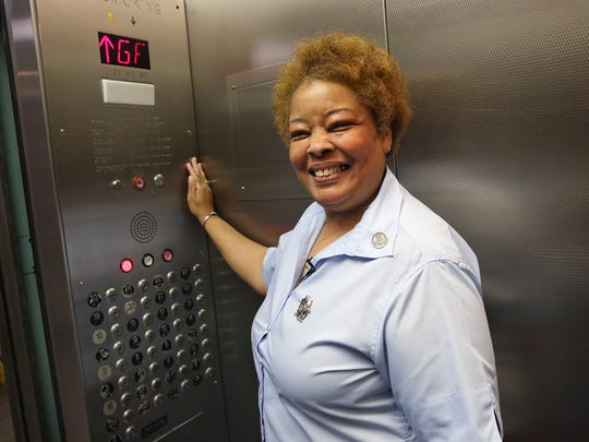 Denise Cummings, a service elevator operator at the City-County Building since 1981, smiles as she operates the elevator.