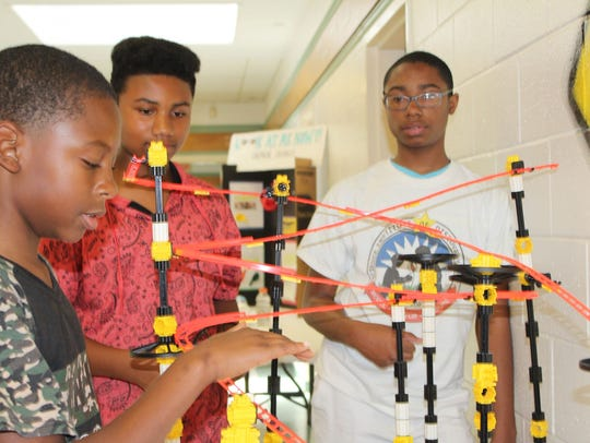 Students show off the Mega Roller Coast they helped