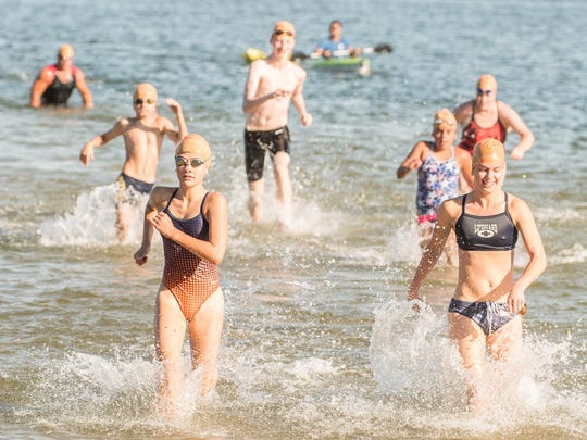 Young competitors run to the finish at Willard Beach for the 90th Annual Goguac Lake Swim on Saturday.