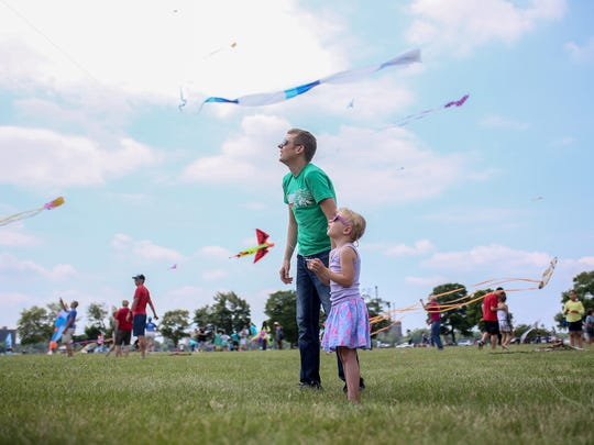 Matt Read, 36, and his daughter Lucy 4, of Birmingham, Mich fly a kite, during the inaugural Detroit Kite Festival held at Belle Isle in Detroit on Sunday, July 16, 2017.