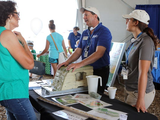 Darrell McCauley (middle) and Savannah Williams (right) talk to Farm Technology Days guests about water movement through Karst landscapes in the UW-Extension tent on July 12. UW Extension workers have been a mainstay at large agriculture shows across the state.