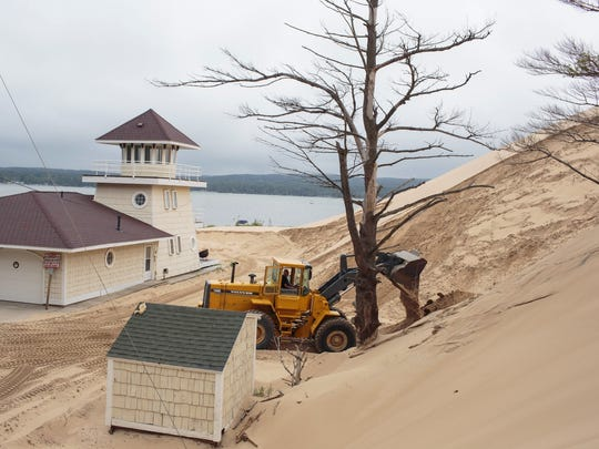 In a July 13, 2017, photo, sand is removed from the location where one cottage was swallowed by an approximately 80-foot tall dune in April at the edge of the Silver Lake Lake State Park in Mears, Mich.