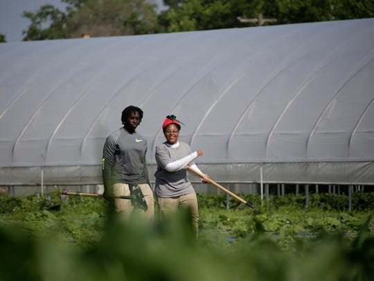 Dakarai Washington, 16, of Detroit, left, and Michael Peeples, 15, of Detroit make their way out to the corn fields at Drew Farms in Detroit to help weed Tuesday July 18, 2017.