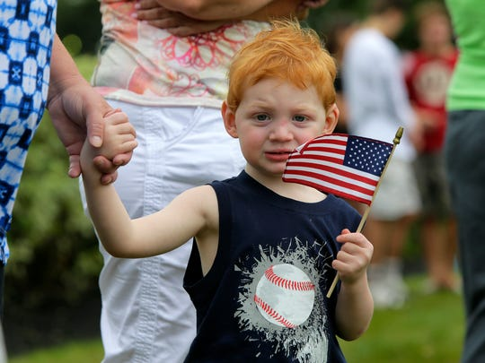 Shane Larkin, 2, of Freehold Twp. holds an American flag as motorcycle riders escort the body of 20-year-old Cpl. Dan Baldassare of Colts Neck, a U.S. Marine who died in a plane crash earlier this month, to Clayton & McGirr Funeral Home in Freehold, NJ from the Dover Air Force Base in Delaware Monday, July 24, 2017.