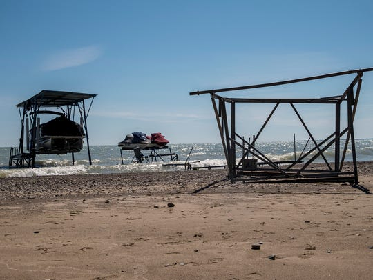 Damaged boats, lifts and dock line a beach on Lake