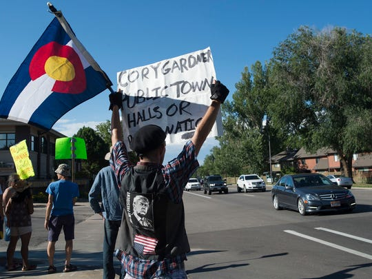 "Jake Knebel, a Colorado resident from Fairplay, holds a sign up to passing traffic on July 27 during the ""Rally to Stop TrumpCare"" hosted by Fort Collins for Progress, outside of Sen. Cory Gardner's office in Fort Collins."