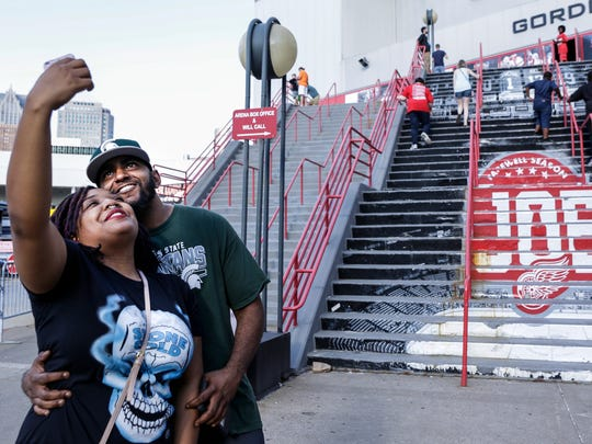 Zinani White, far left, takes a selfie with her husband Malcoum White, both of Detroit, outside of Joe Louis Arena, Saturday, July 29, 2017, in Detroit.