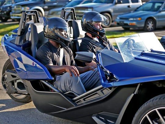 Vontae Davis, left, arrives in a Slingshot roadster