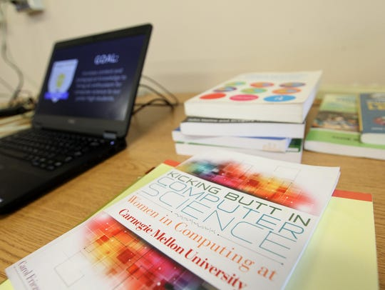 Computer science books are spread across a table during
