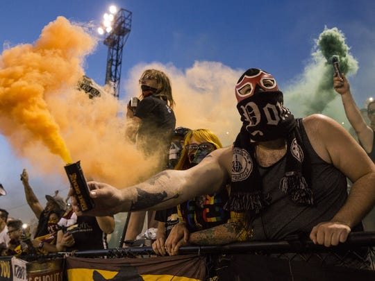 Abe Dorow, also known as Mustachio, center right, holds a smoke bomb at the 85th minute of the friendly game between Detroit City FC and Venezia FC (Italy) at Keyworth Stadium, Tuesday, July 18, 2017 in Hamtramck.