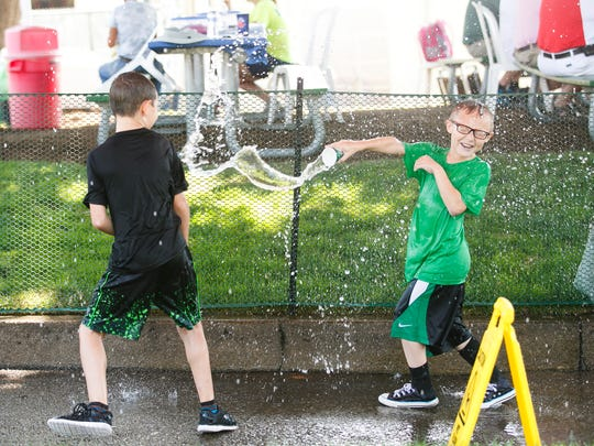 Mason Buckholz, left, and Caden Hubbard, right, play in a sprinkler tent at the USA Softball 18A National Championship on Wednesday, Aug. 2, 2017, at Wallace Marine Park in Salem, Ore. Temperatures on Wednesday reached triple digits in the afternoon.