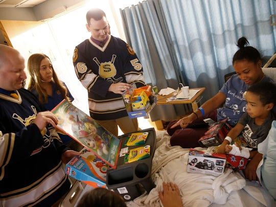 New Jersey State Policemen's Benevolent Association Hockey team members Daniel Tacopino (left) and Brian Oeckel join Daniela Olt, 15, of 'Daniela's Wish' in delivering toys to K. Hovnanian Children's Hospital patient Darien Fitzgerald, 4, and his mother Stardasia Williams on Monday, August 7, 2017.  Tacopino is a Monmouth County Sheriff's officer and Oeckel is from the NJ Juvenile Justice Commission.