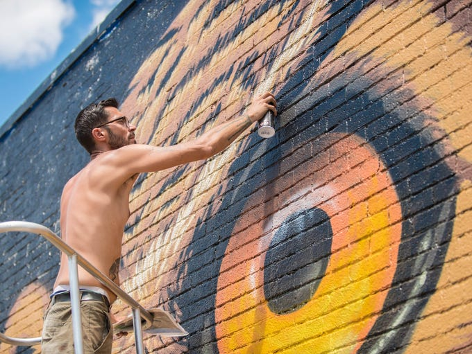 Justin Suarez from Rochester works on a mural at Capital
