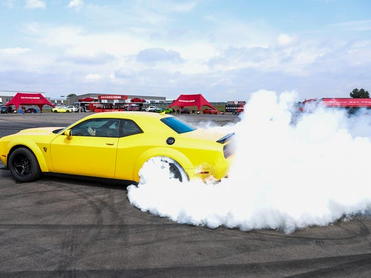 A 2018 Dodge Challenger SRT Demon does a smokey burnout during the Roadkill Nights preview event at M1 Concourse Race Track in Pontiac, Friday, August 11, 2017. The Demon is driven by Tim Kuniskis, FCA's Head of Passenger Car Brands.