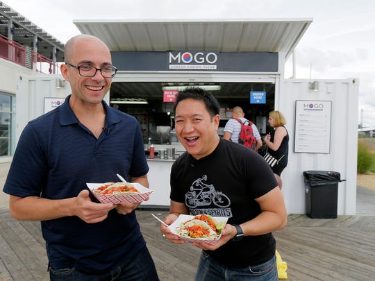 """Alex Biese, features reporter at Asbury Park Press, and Ming Chen, co-host of """"Comic Book Men"""" on AMC, eat Korean fusion tacos at MOGO on the boardwalk as they spend the day in Asbury Park, NJ with only $100 for """"Travel Allowance,"""" a new USA Today project, Tuesday August 8, 2017."""
