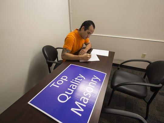 Inmate Jacob Quintana fills out a job application at