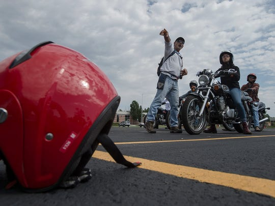 Motorcycle Safety Foundation instructor Joe Nesselroth instructs student Nina Belanio where to walk her training motorcycle during a lesson, Saturday, August 12, 2017 in the parking lot of Front Range Community College in Fort Collins, Colo.