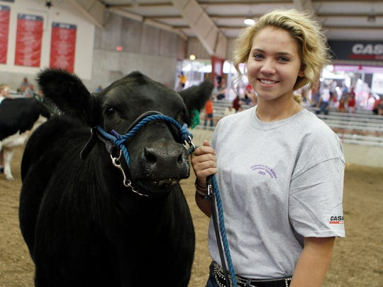 Katie Leahy, of Lafayette County, waits with her Grand Champion Maine-Anjou Steer, at the Governor's Blue Ribbon Livestock Auction on Aug. 9 at the Wisconsin State Fair.