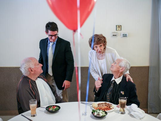 John Wearing, bottom right talks with Grace Kennedy, 78, of Grosse Pointe Park as he eats next to Father Donald Worthy and Anthony Seely, 22, of Grosse Pointe, during John Wearing's life celebration at the Bruce VFW Post in St. Clair Shores, Mich., on Sunday, Aug. 13, 2017.