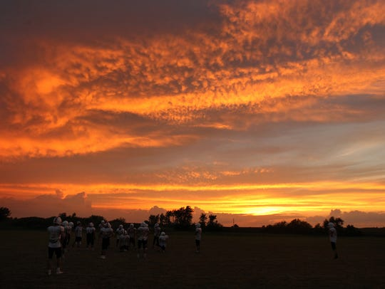Highland players run plays as the sun sets during practice