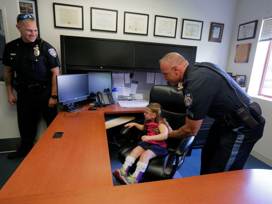 Lara Marini, 6, one of two siblings of Long Valley who live with Cockayne Syndrome, sits in the office of the police chief, with the help of SGT Robert Oranchak, as she tours the Washington Township Police Department with her family in Long Valley, NJ Wednesday August 16, 2017.