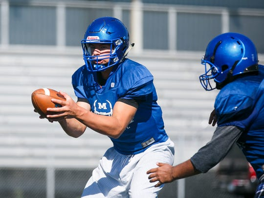 Eric Barker hands off the ball at a McNary High School