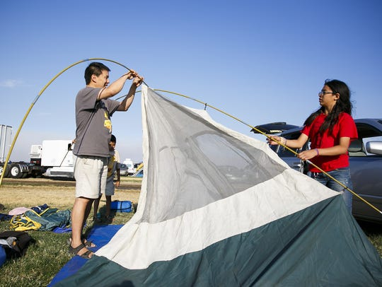 Sam Cheng, left, and Isabelle, 11, right, set up a