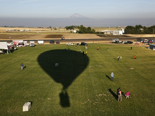 The shadow of Brann and Marie Smith's hot air balloon covers the lawn at Solartown on Sunday, Aug. 20, 2017.