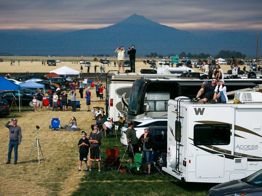 Spectators watch the beginning of totality from Solartown, a solar eclipse campground, on Monday, Aug. 21, 2017, just north of Madras, Ore.