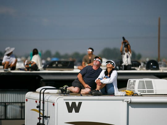 Mike Flynn and Nona Dyck watch the sun as the eclipse approaches totality in Solartown, a solar eclipse campground, on Monday, Aug. 21, 2017, just north of Madras, Ore.