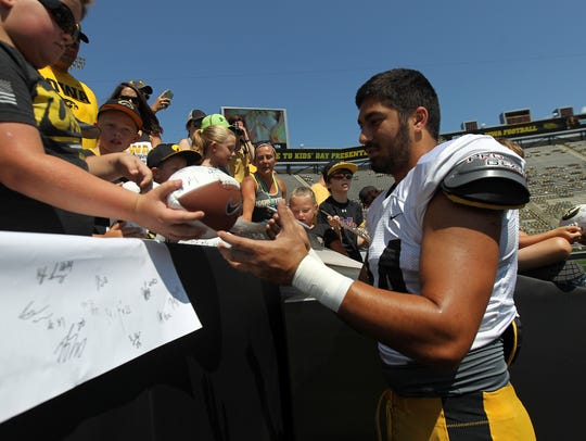 Iowa's A.J. Epenesa signs autographs during the open