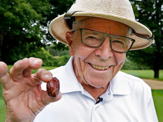 """Frank Swingle holds a date and says his famous line, """"Want a date?"""" while at Meridian Hills Country Club's hole #12, Tuesday, August 22, 2017.  The 93-year-old golfer recently made a hole-in-one on this hole."""