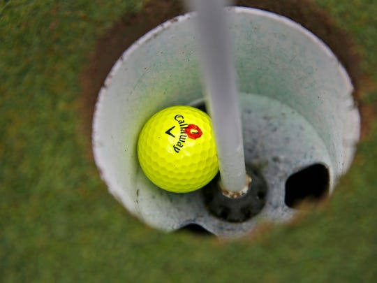One of Frank Swingle's yellow balls sits in the cup at Meridian Hills Country Club's hole #12.  The 93-year-old golfer recently made a hole-in-one at this hole, seen Tuesday, August 22, 2017.