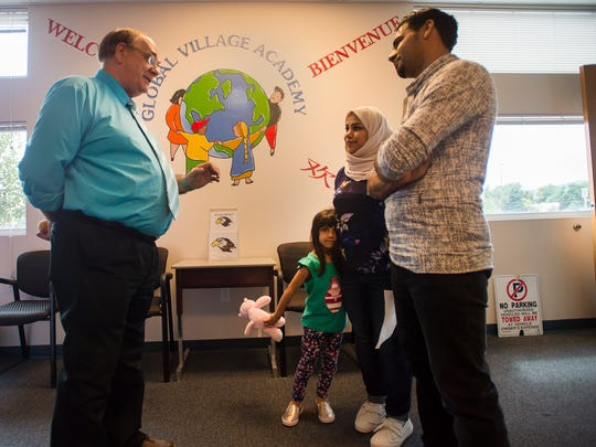 New principal Dave Finley, left, speaks with parents Aziz and Khadija Alrahpi about their daughter Athir, 4, before Athir takes a baseline test to see where she is on her educational development during the first day of school at Global Village Academy, Wednesday, Aug. 23, 2017, in Fort Collins.