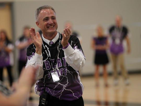 Liberty High Principal Scott Kibby applauds as faculty
