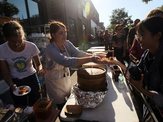 Cede Angel serves food to a guest at Dumpling Darling during Taste of Iowa City on Wednesday, Aug. 23, 2017.