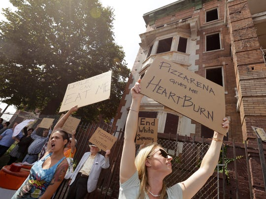 Mariel Collins, left and Amy Swift, right both of Detroit chant and hold signs in front of the Atlanta building on Cass Avenue to raise awareness about the value of preserving historic buildings and asked that a group of buildings including the Atlanta and Hotel Ansonia not be demolished in Detroit on Thursday, August 24, 2017.