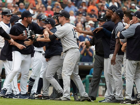 Players and coaches hold back Detroit Tigers starting pitcher Justin Verlander  after benches clear when catcher James McCann (not pictured) was hit by a pitch from New York Yankees relief pitcher Dellin Betances (68) in the seventh inning at Comerica Park.