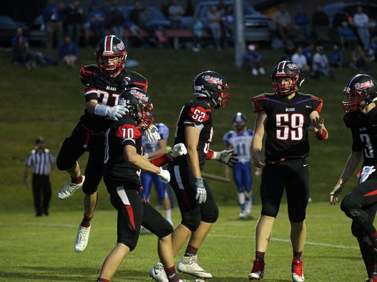 West Branch teammates celebrate with Ben Thompson (10) after his touchdown during the Bears' game against West Liberty in West Branch on Friday, Aug. 25, 2017.