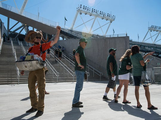 Beer hawker Rob Hayes holds his fist up while interacting with a fan before Colorado State University football's season opening game against Oregon State, Saturday, August 26, 2017, at Sonny Lubick Field at Colorado State Stadium in Fort Collins, Colo.