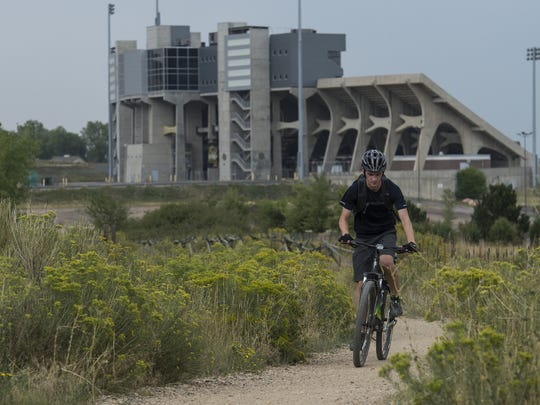 A cyclist makes his way South on the Foothills Trail past Hughes Stadium, Tuesday, August 30, 2017, at Maxwell Natural Area in Fort Collins, Colo.