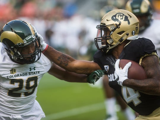 CU receiver Bryce Bobo (4) delivers a stiff arm to CSU cornerback Justin Sweet (29) Friday, September 1, 2017, during the Rocky Mountain Showdown at Sports Authority Field at Mile High in Denver, Colo.