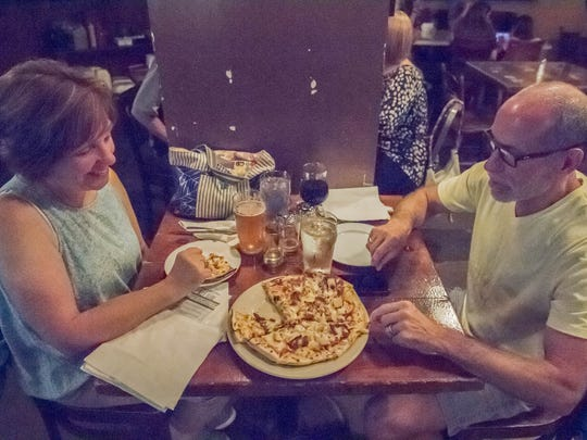 Karen and Kevin Rabineau enjoy some pizza during the last night for Arcadia at the 103 W. Michigan Ave. location in Battle Creek Saturday night.