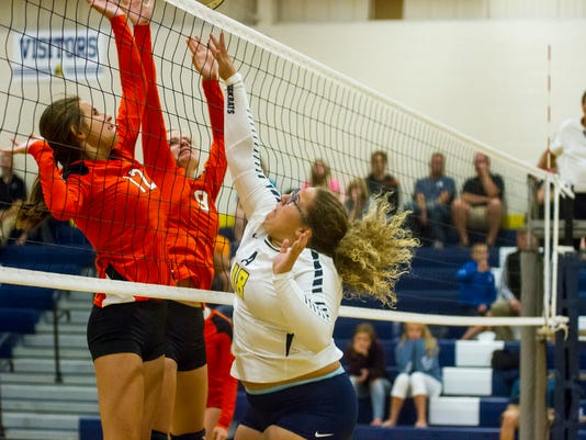 Algonac's Abi Folkerts (18) fights Marine City's Destiny Biland (12) and Madison Morse during their game Sept. 5.