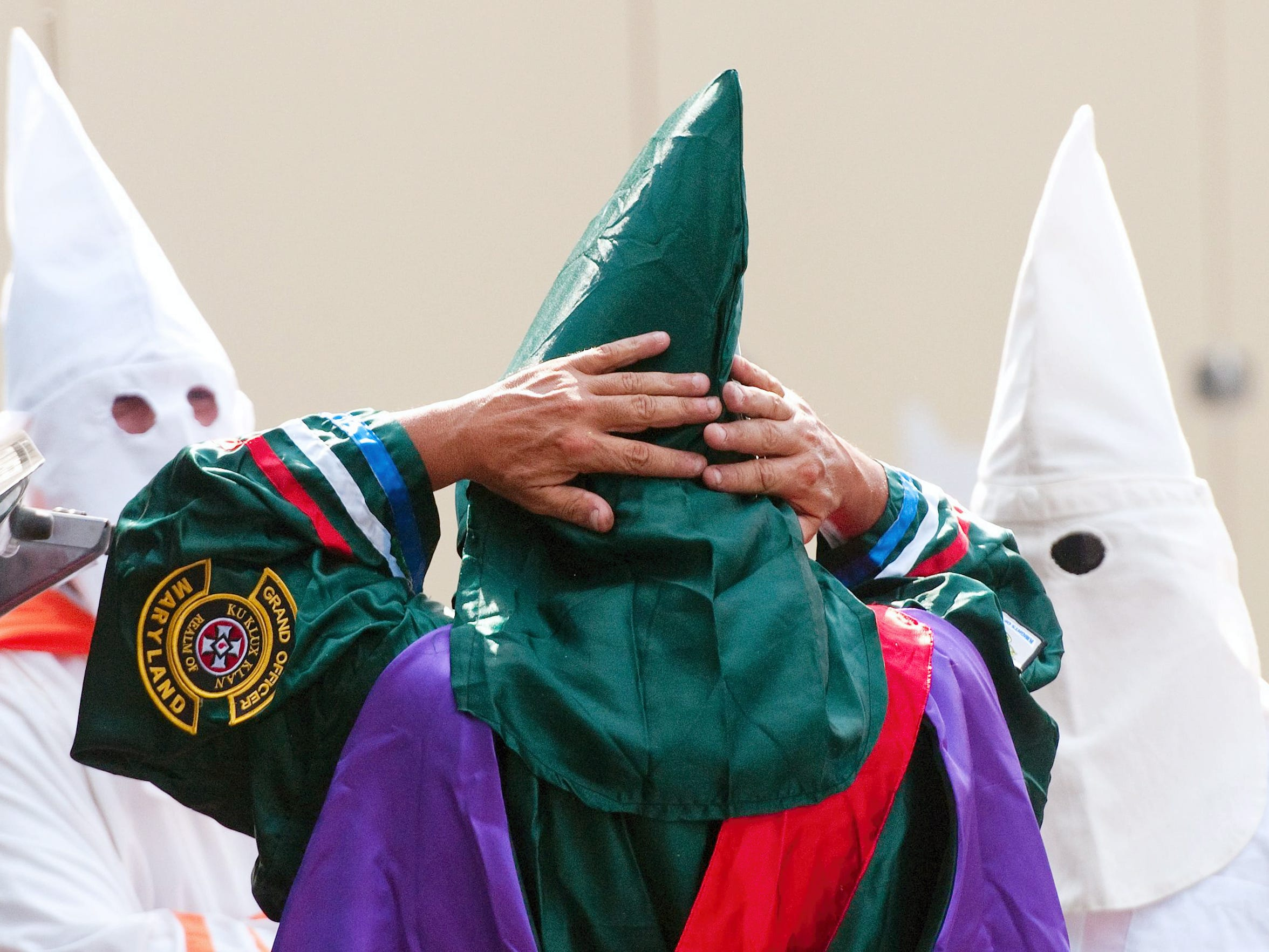 A member of the Confederate White Knights of the Ku Klux Klan who would not identify himself puts on his hood and robe as others look on after arriving outside the borough office in Gettysburg, Pa., Saturday, Oct. 5, 2013. The group previously requested a permit to demonstrate at Gettysburg National Military Park, but that permit was revoked as a result of the federal government shutdown.
