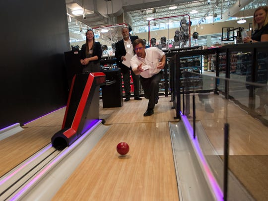 Members of the media try out a miniature bowling lane