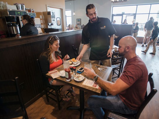 Food runner Dan Roschen, center, serves a plate to Amber Kahler and Bryon Jones, Thursday, Sept. 7, 2017, at the soft-opening for the Famous Toastery on East Harmony Road in Fort Collins, Colo.