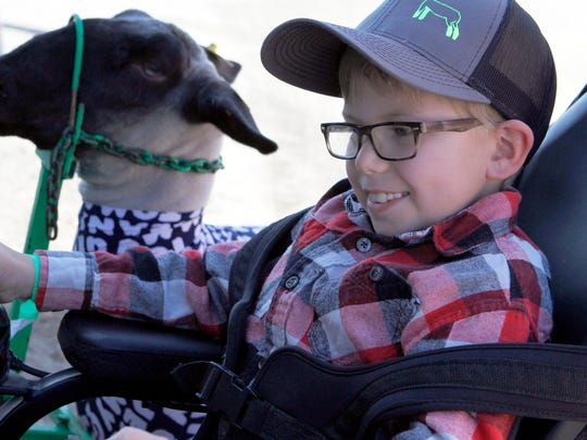Braden Pederson. 10, of Cashton, leads his sheep out of a barn at the Jeffeson County Fairground on Sept. 9. Braden, who was born with spina bifada, always wanted to be a farmer.