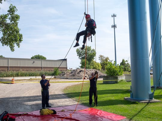 Port Huron firefighters Kyle Brunk, left, and Roger Howison, right, help Bruce Holt as he rappels from a water tower on Bancroft Street as part of a rope training exercise Sept. 12.
